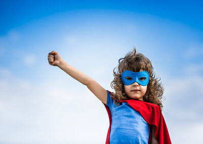 Superhero child against blue sky background